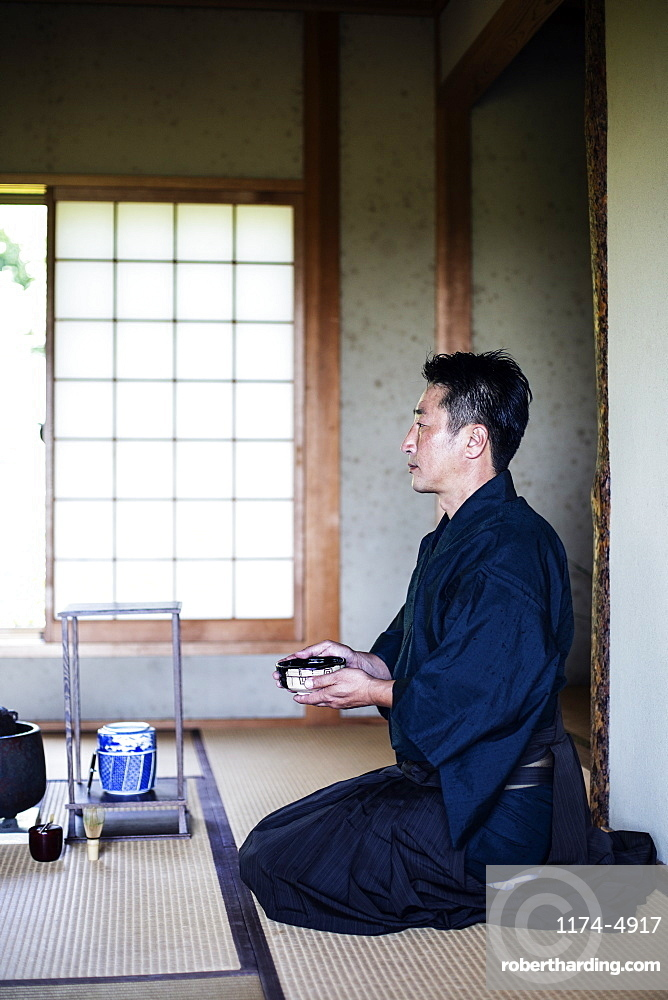 Japanese man wearing traditional kimono kneeling on floor, holding tea bowl, during tea ceremony, Kyushu, Japan
