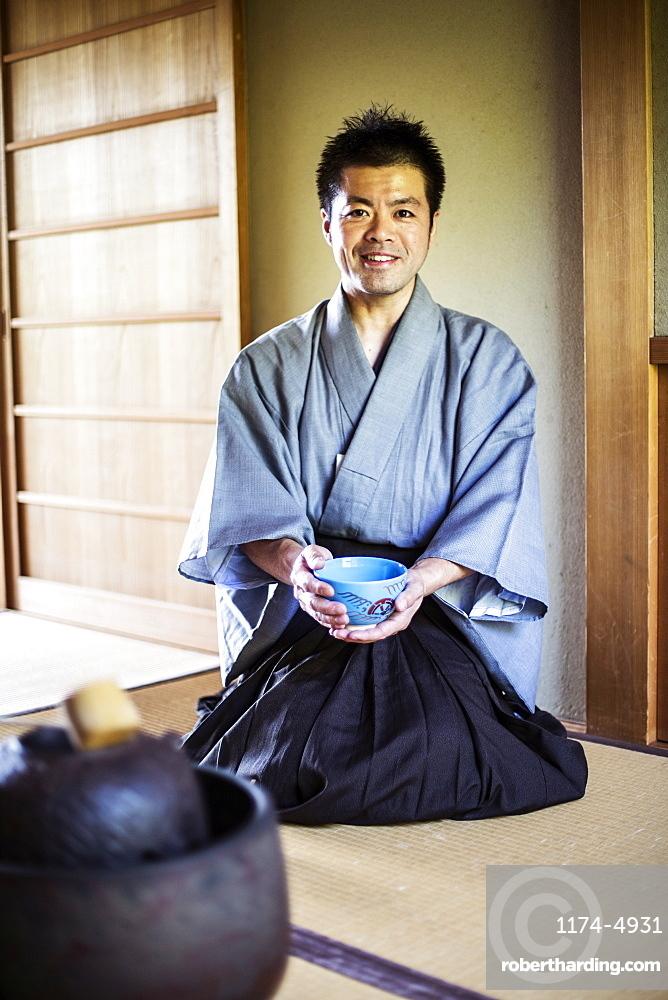Japanese man wearing traditional kimono kneeling on floor, holding blue tea bowl during tea ceremony, Kyushu, Japan