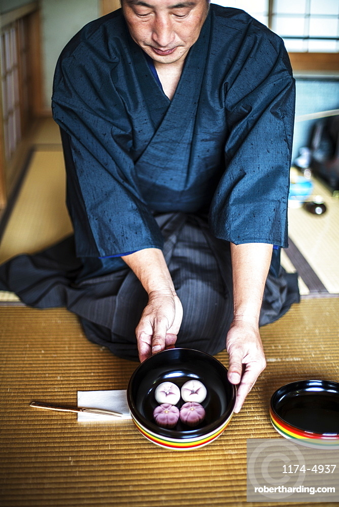Japanese man wearing traditional kimono knelling on floor, holding a bowl with Wagashi, sweets traditionally served during a Japanese Tea Ceremony, Kyushu, Japan
