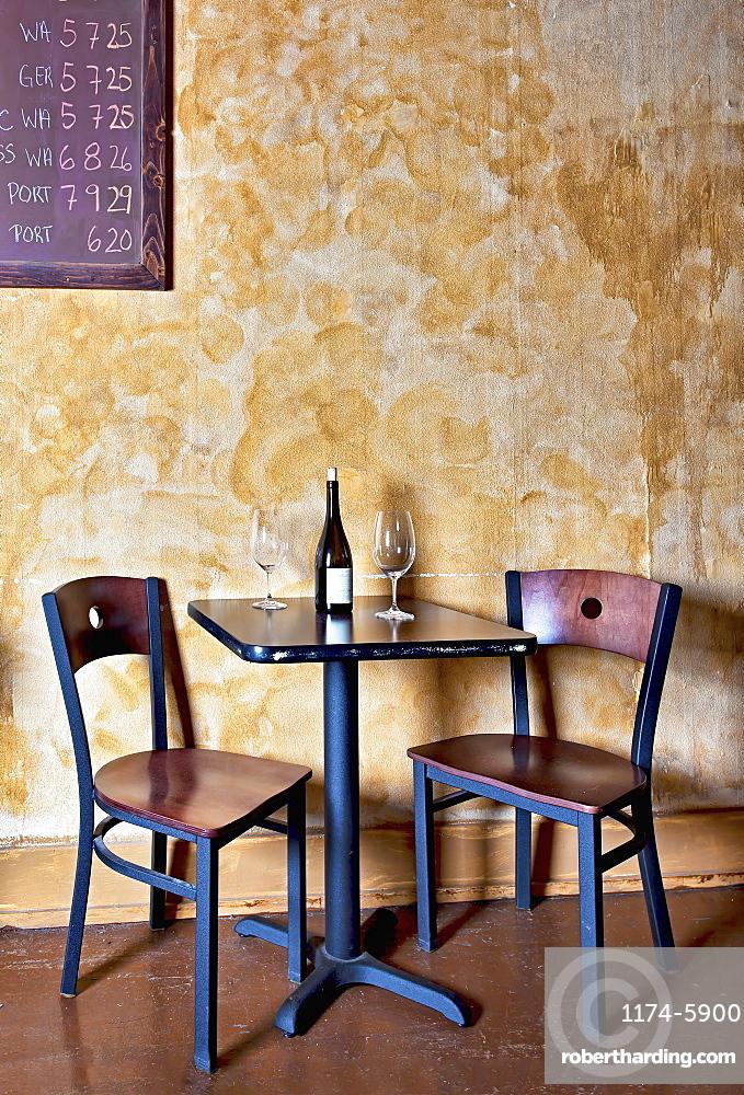 Bottle of wine and glasses on table in wine bar, Oregon, Washington, USA