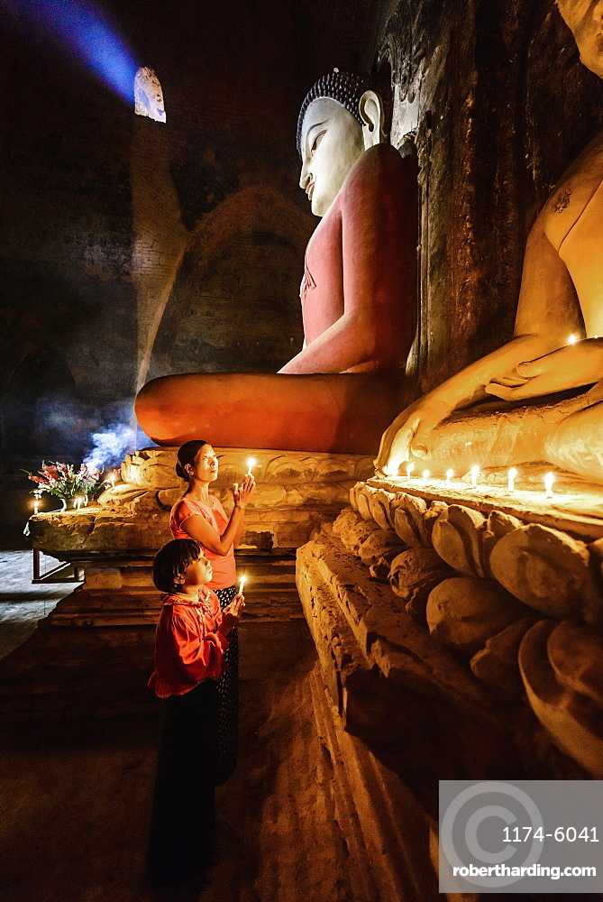 Asian mother and daughter lighting candles in temple