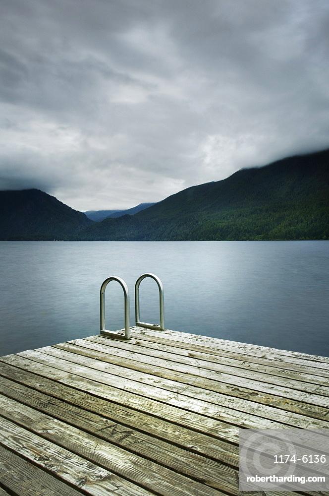 Ladder on wooden pier near still remote lake