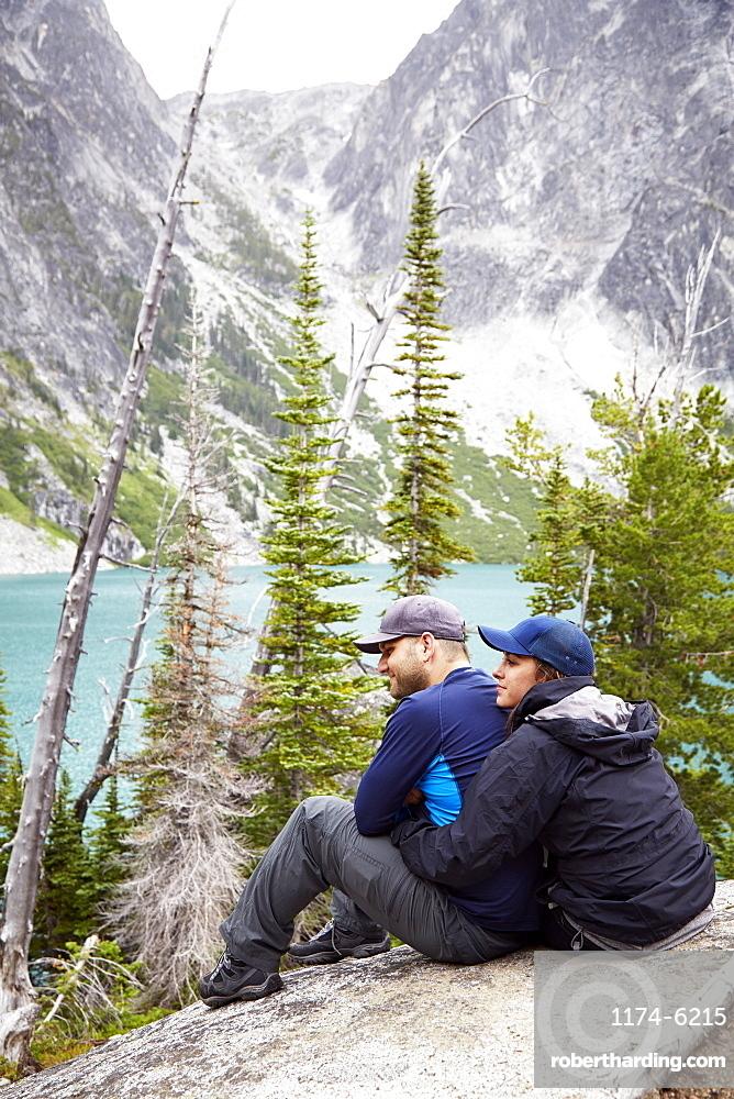 Couple admiring mountains and remote lake, Leavenworth, Washington, USA