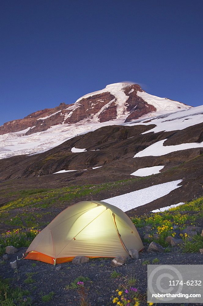 Glowing tent at campsite in remote landscape, North Cascades, Washington, USA
