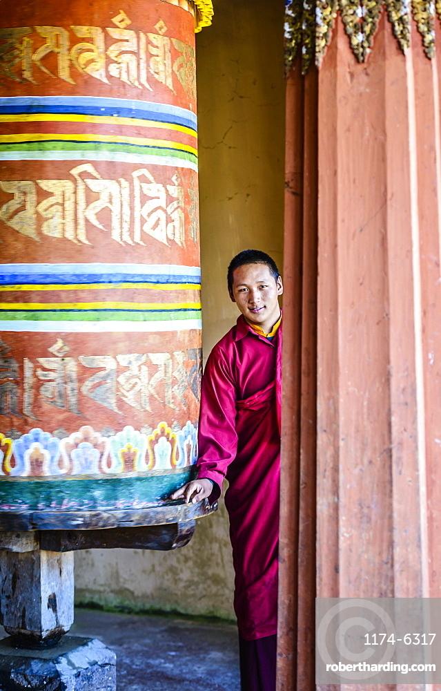 Asian monks standing by pillar in temple, Bhutan, Kingdom of Bhutan