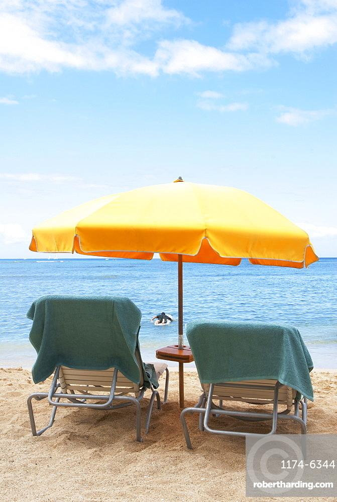 Lawn chairs and umbrella on beach, Honolulu, Oahu, USA