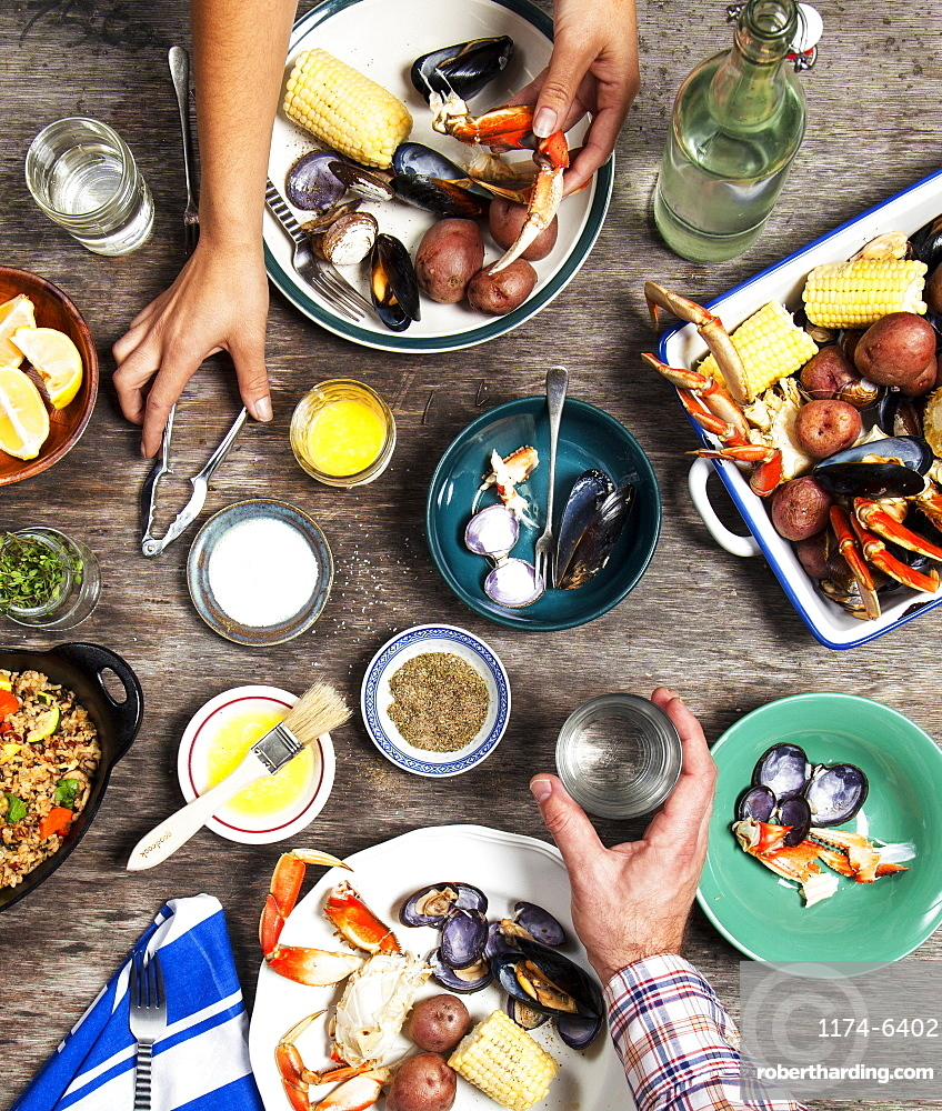 High angle view of hands at seafood dinner, Seattle, Washington, USA