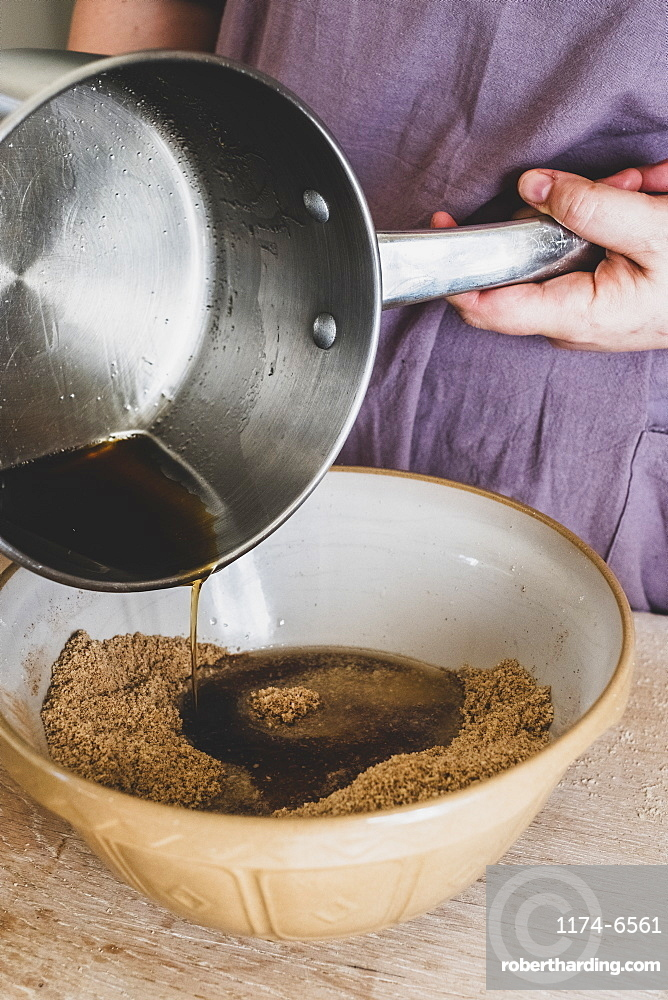 High angle close up of person pouring liquid into mixing bowl with baking ingredients, England