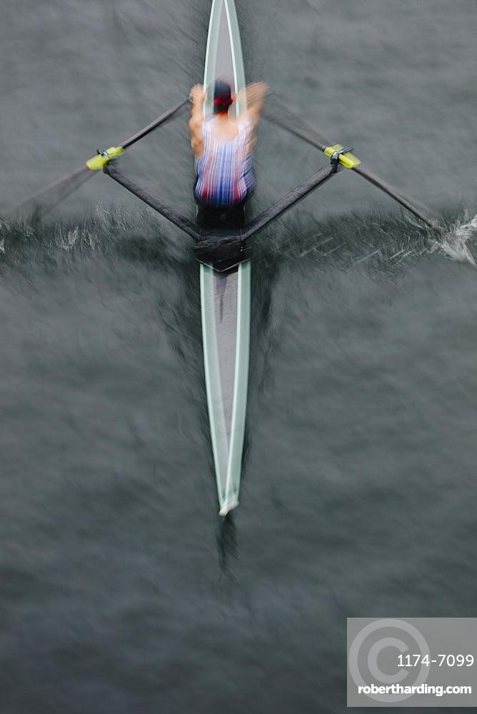 Overhead view of an oarsman in a single scull boat on calm water mid stroke, motion blur