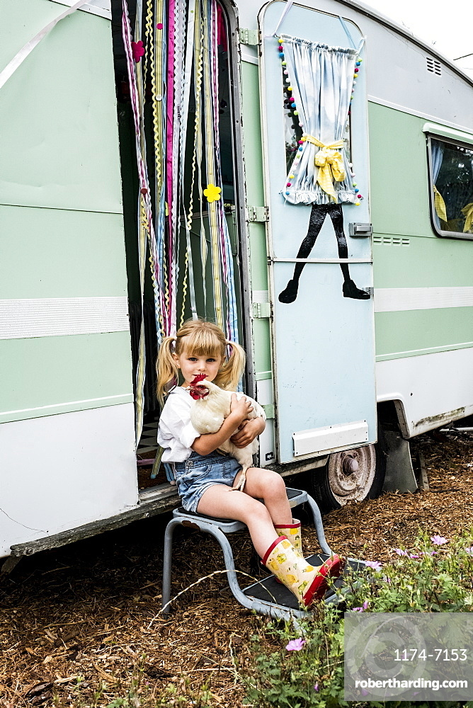 Blond girl holding white chicken sitting outside a caravan