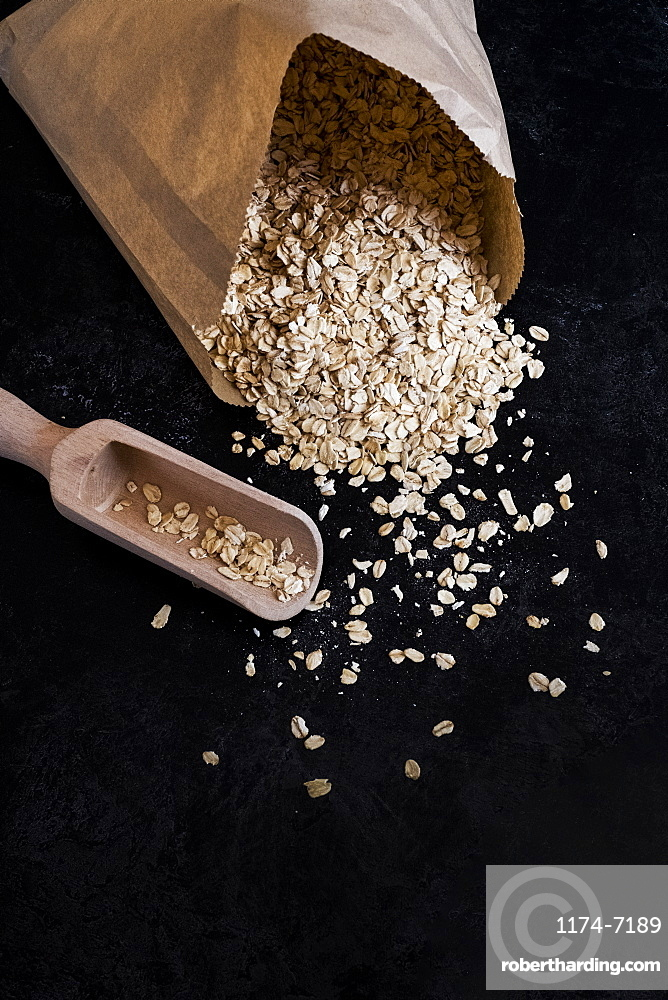 High angle close up of paper bag with oats and wooden spoon on dark background