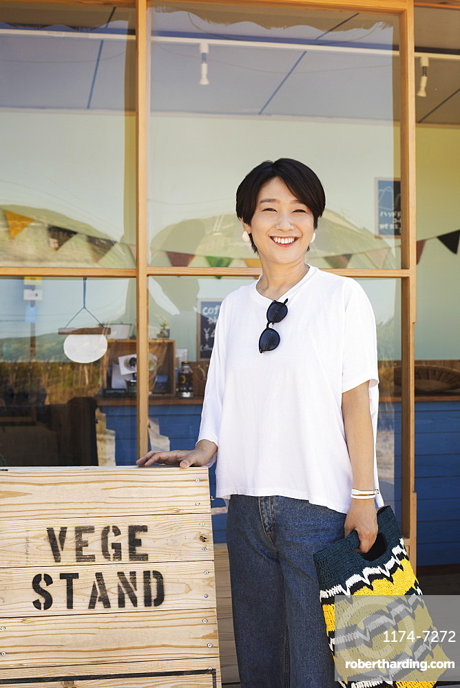 Japanese woman standing outside a farm shop, holding shopping bag, smiling at camera, Kyushu, Japan