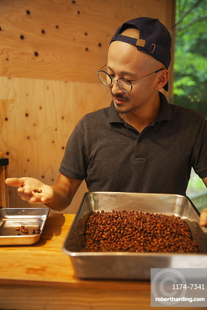 Japanese man wearing baseball cap and glasses standing in an Eco Cafe, checking freshly roasted coffee beans, Kyushu, Japan