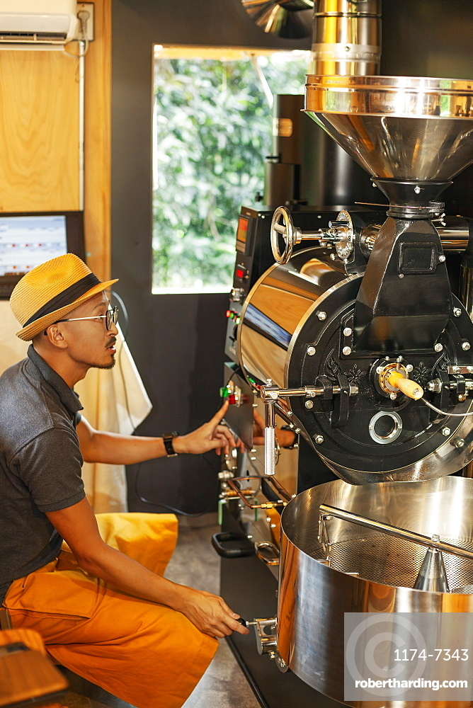 Japanese man wearing hat and glasses sitting in an Eco Cafe, operating coffee roaster machine, Kyushu, Japan