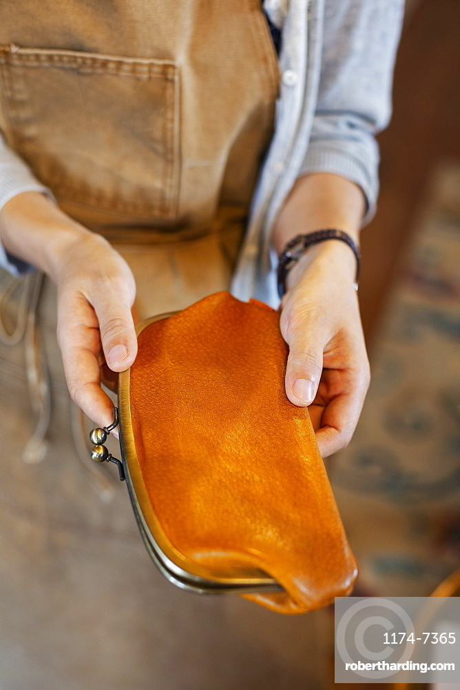High angle close up of person standing in a leather shop, holding an leather purse, Kyushu, Japan