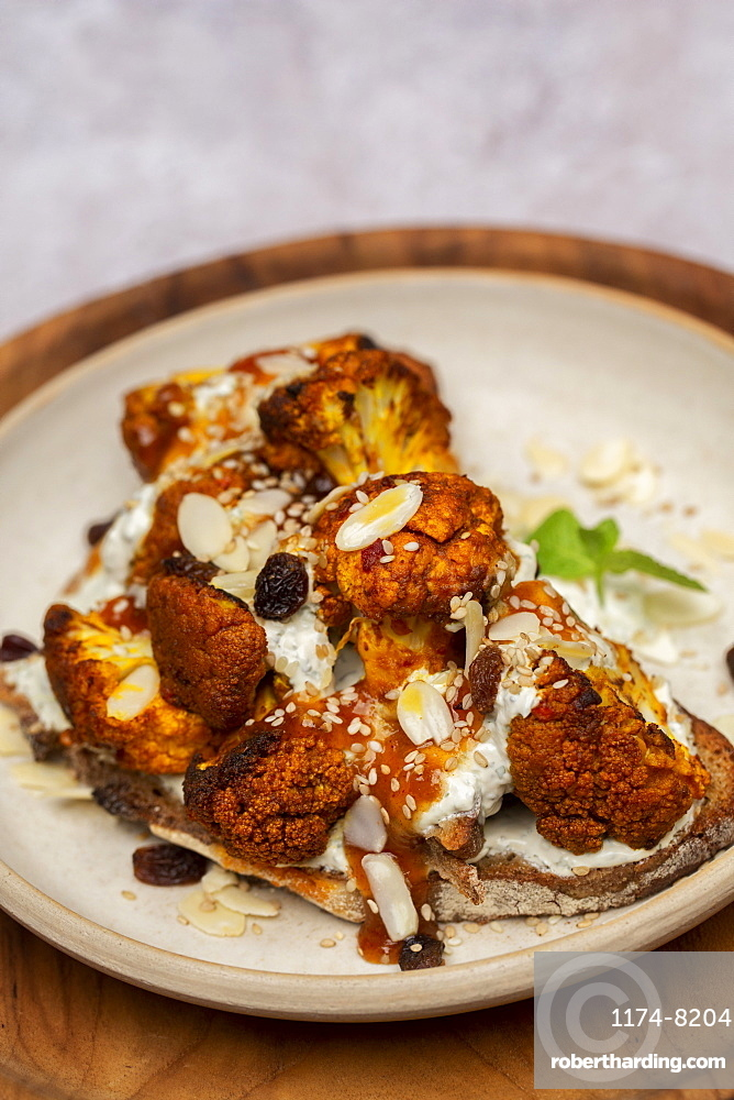 High angle close up of roasted cauliflower on toasted sourdough bread on a plate