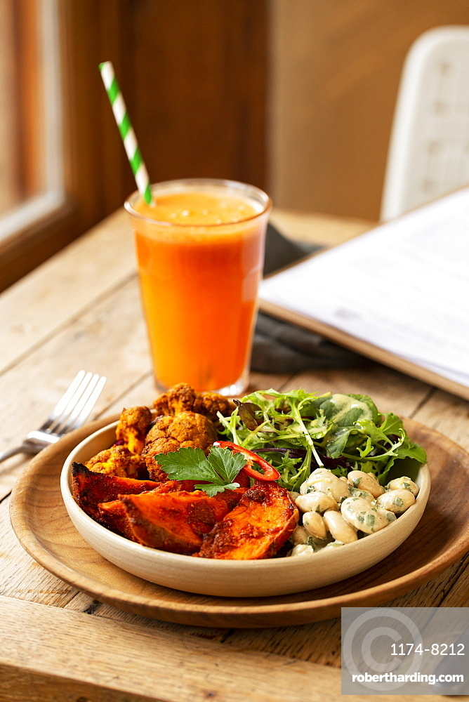 High angle close up of glass of carrot juice and bowl of mixed vegetables in a cafe