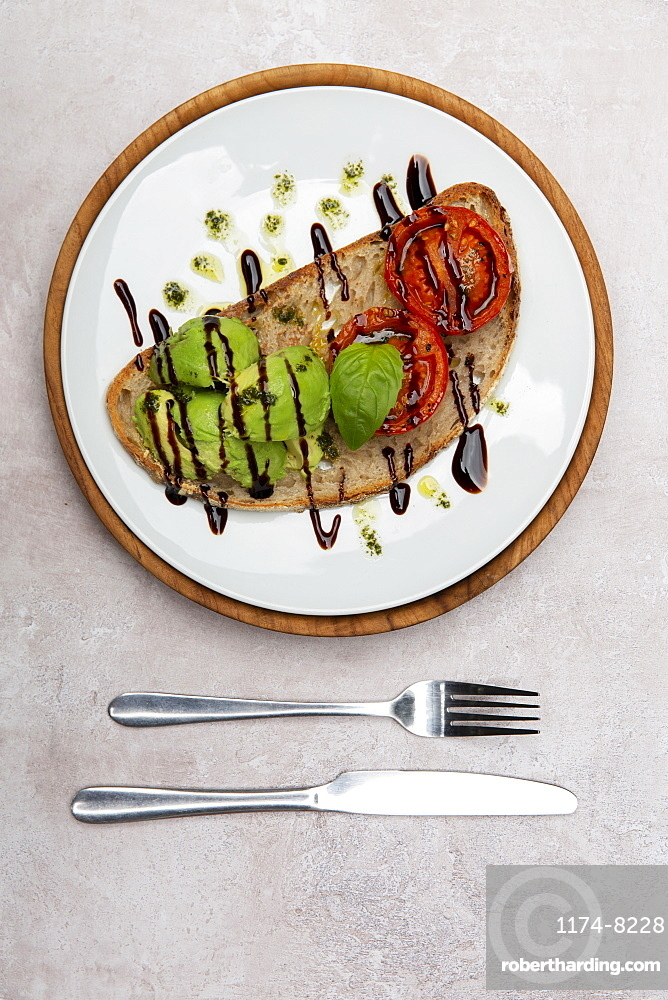 High angle close up of tomato and avocado bruschetta with balsamic vinegar reduction in a cafe
