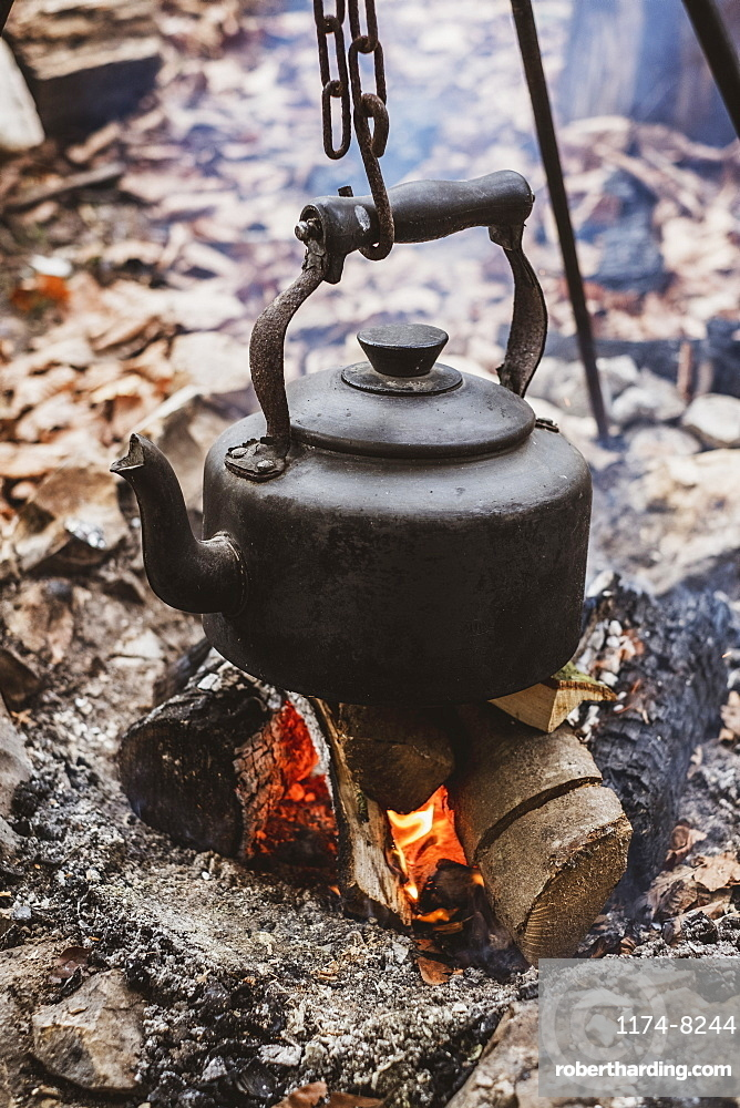 High angle close up of kettle over camp fire in a forest, Devon, United Kingdom