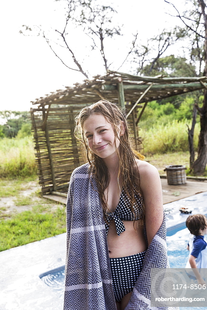 Smiling Thirteen year old girl by a swimming pool in a safari resort