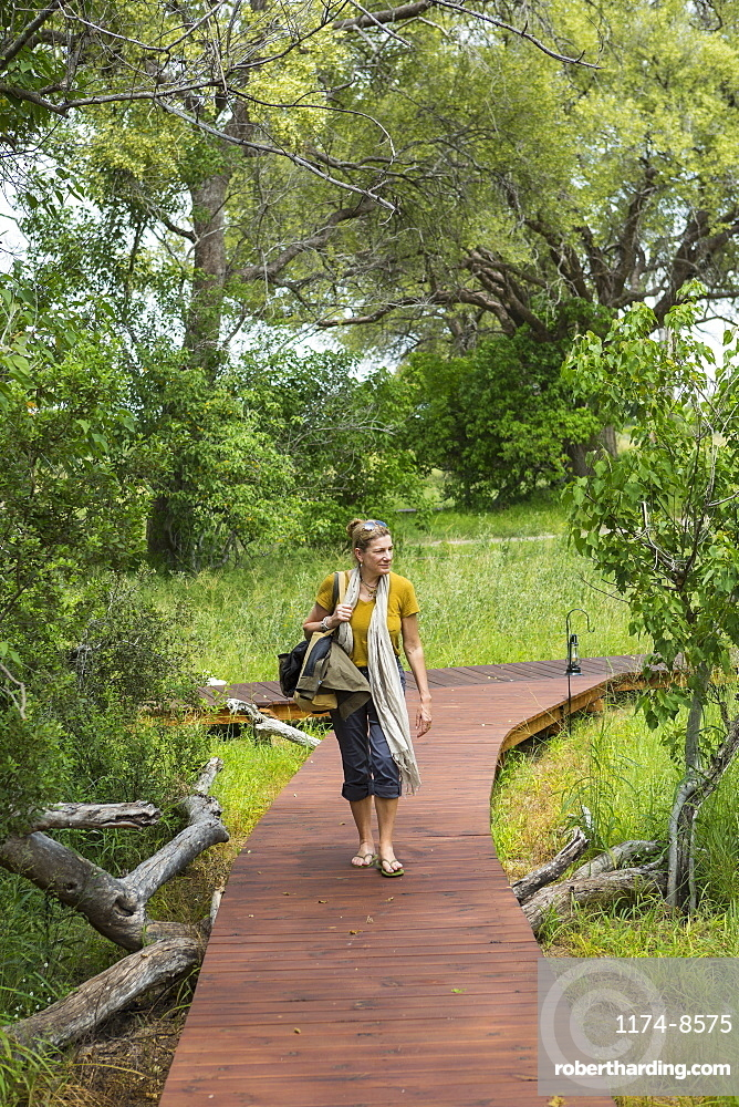 adult woman walking wooden path, tented camp, Botswana