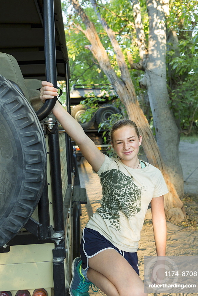 A twelve year old girl getting out of a safari jeep in a wildlife reserve camp, Okavango Delta, Botswana