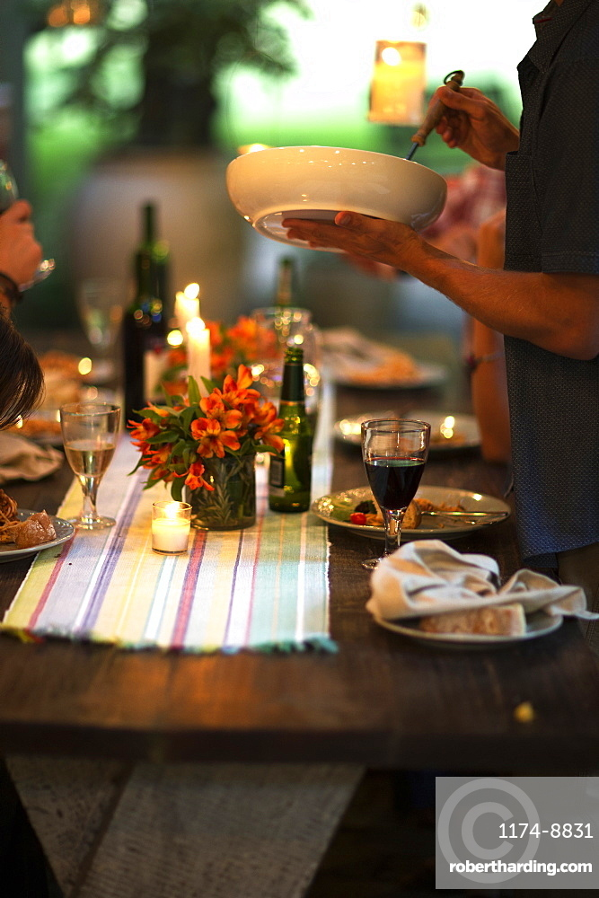 Person standing at a table holding a bowl, wine glasses, plates, flowers and candles on the table