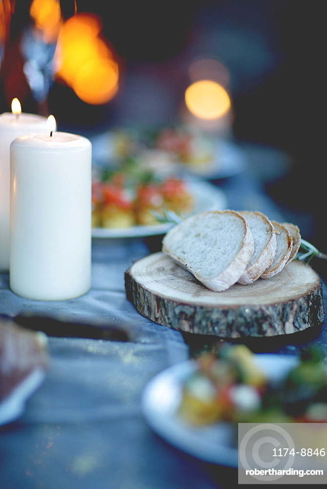 Close up of two lit candles and slices of bread on round wooden board