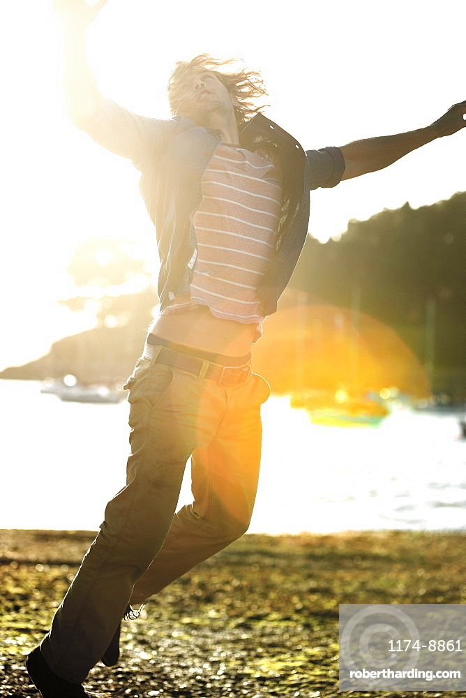 Young man jumping on a pebbly beach, arms raised, moored sailing boats in the background, sunlight, Cornwall, United Kingdom