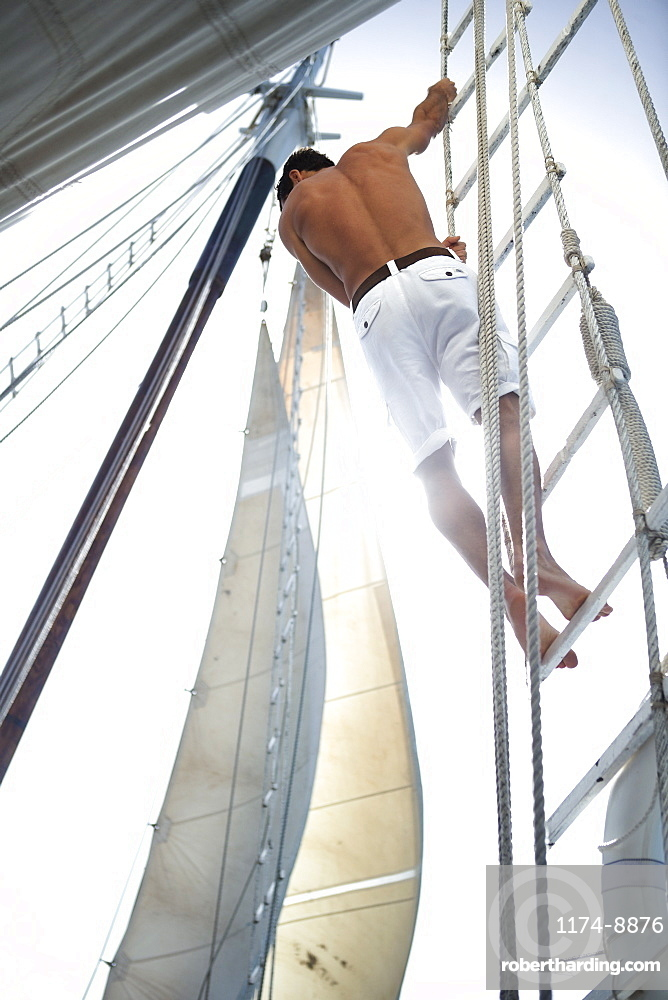 A man in white shorts with bare chest climbing up the rigging of a sailing boat, United States of America