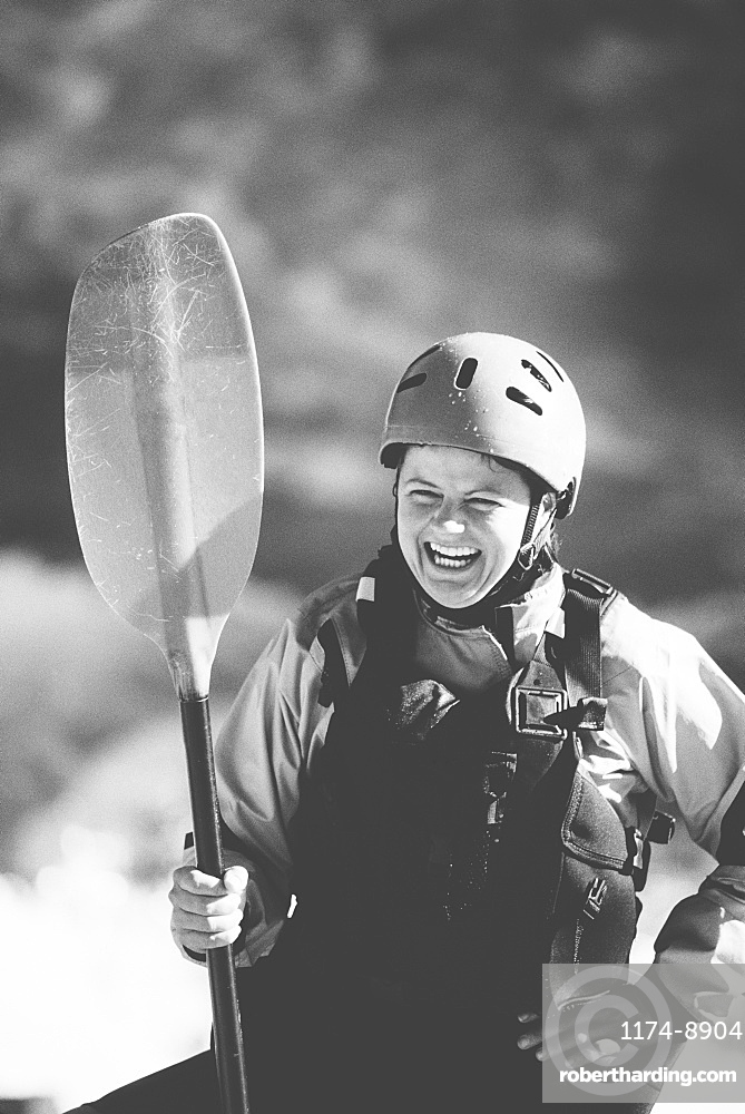 Female whitewater kayaker on a river bank holding a paddle