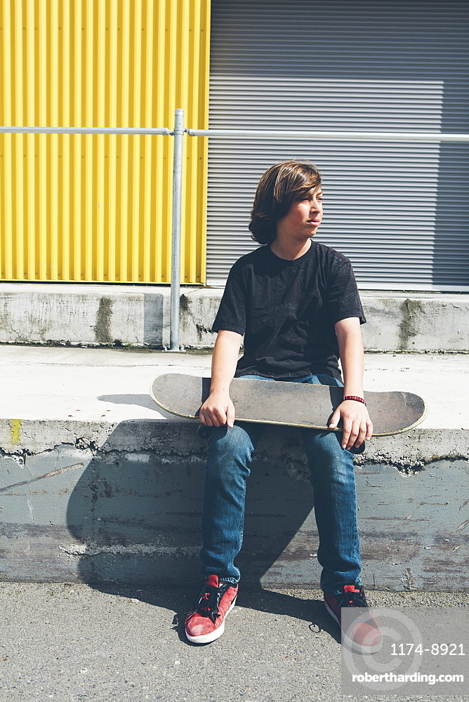 Teenage boy posing siting with skateboard in front urban warehouse