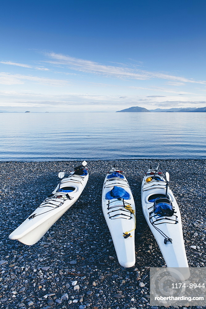 Sea kayaks on remote beach calm waters of Muir Inlet in distance, Glacier Bay National Park and Preserve, Alaska