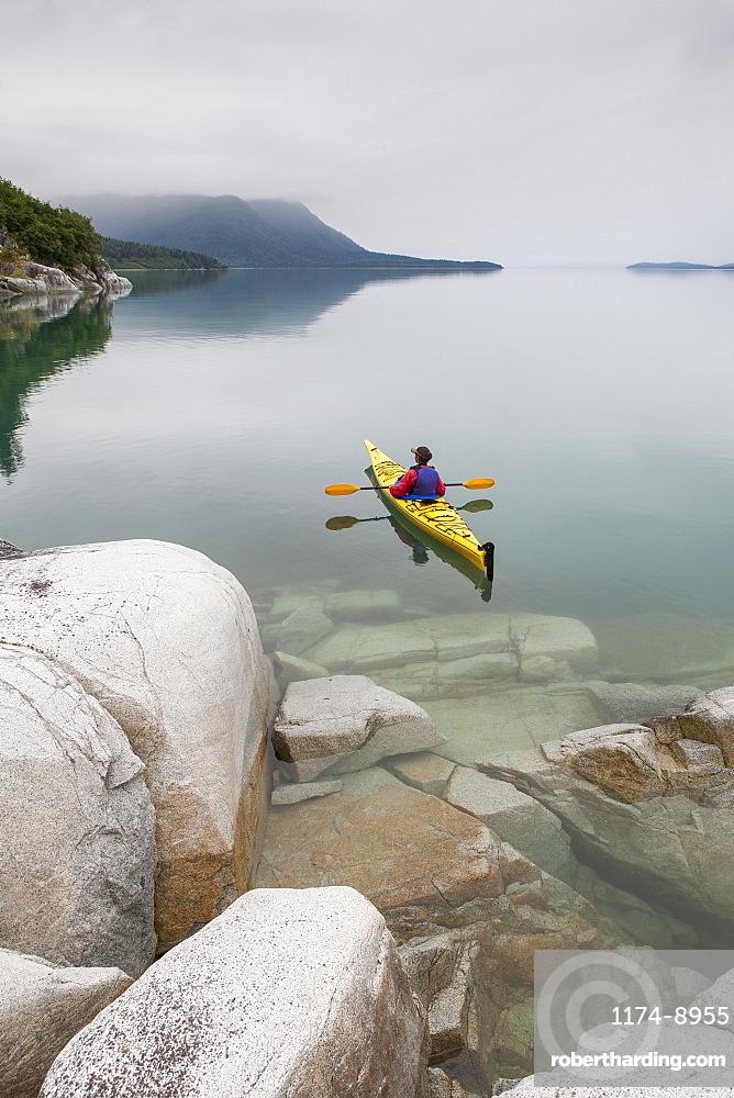 Female sea kayaker paddling pristine waters of Muir Inlet overcast sky in distance, Glacier Bay National Park, Alaska