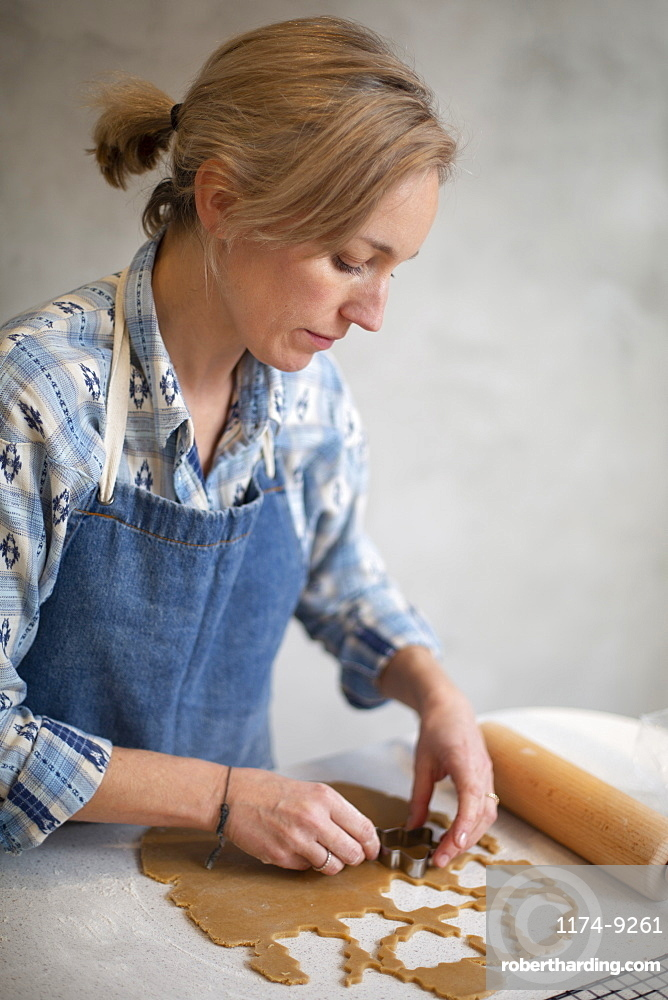 Blond woman wearing blue apron cutting out Christmas cookies