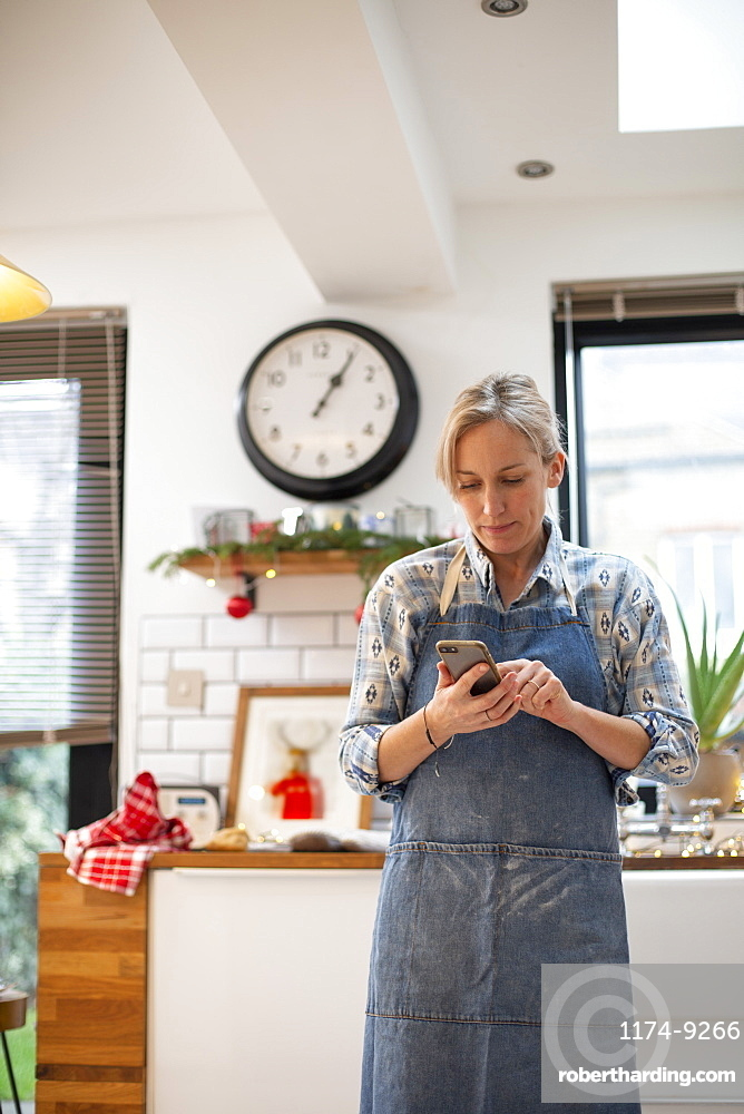 Blond woman wearing blue apron standing in kitchen, using mobile phone