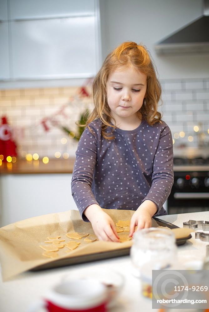 Girl standing in kitchen, baking Christmas cookies