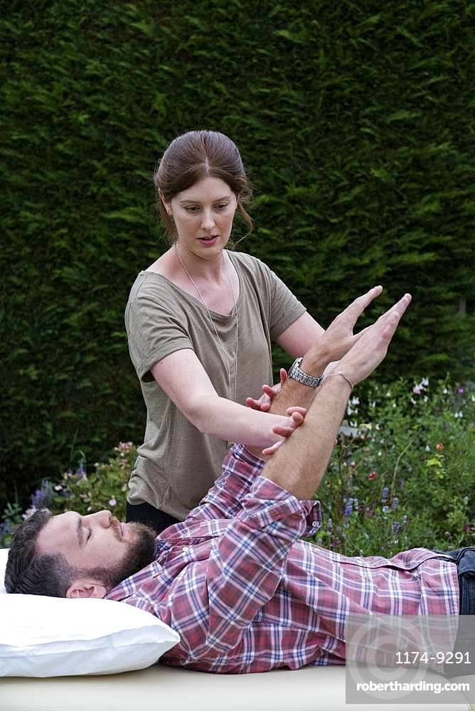 Man on a couch and therapist raising his arms in a garden therapy session