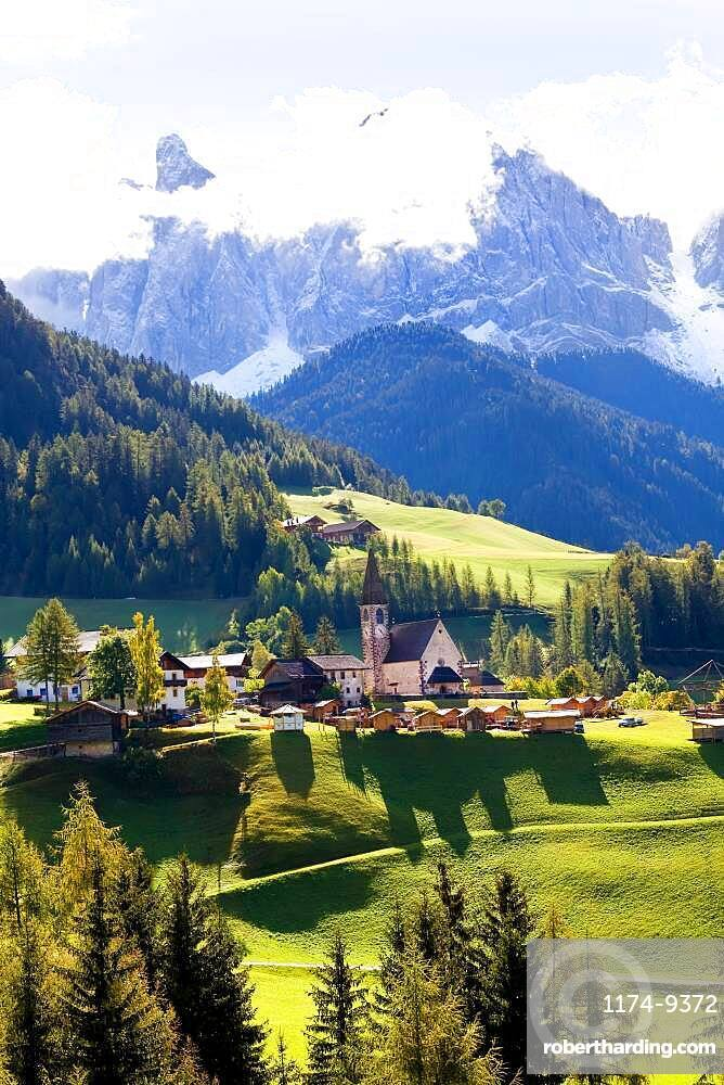 Church in the Val di Funes, alpine valley and mountains in cloud, South Tyrol, Italy