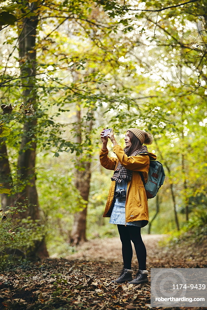 Woman standing on woodland path taking photograph using smart phone