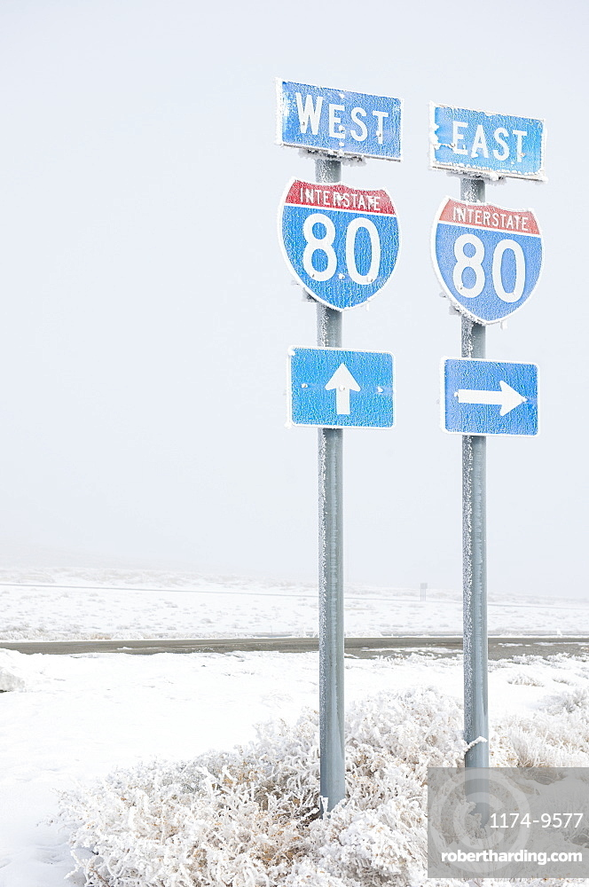 Highway signs on road in wintry snowy landscape