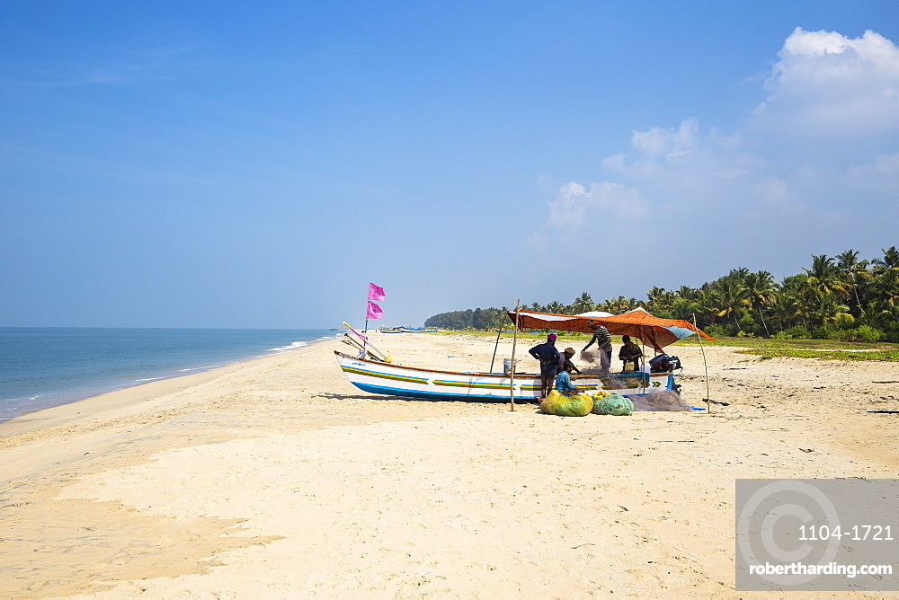 India, Kerala, Alleppey - Alappuzha, Marari Beach, Men sorting out fishing net on boat