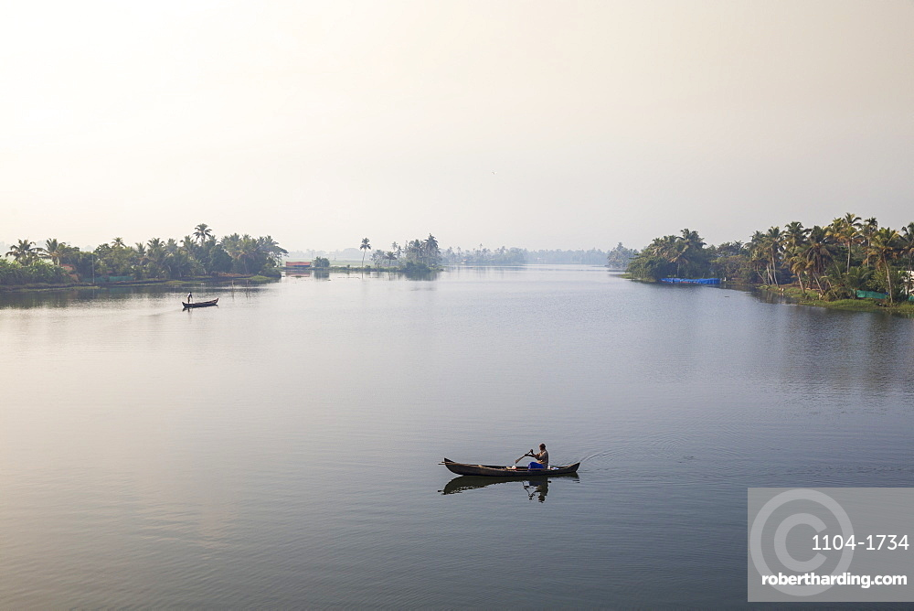 India, Kerala, Alappuzha (Alleppey), Man in dugout canoe on backwaters