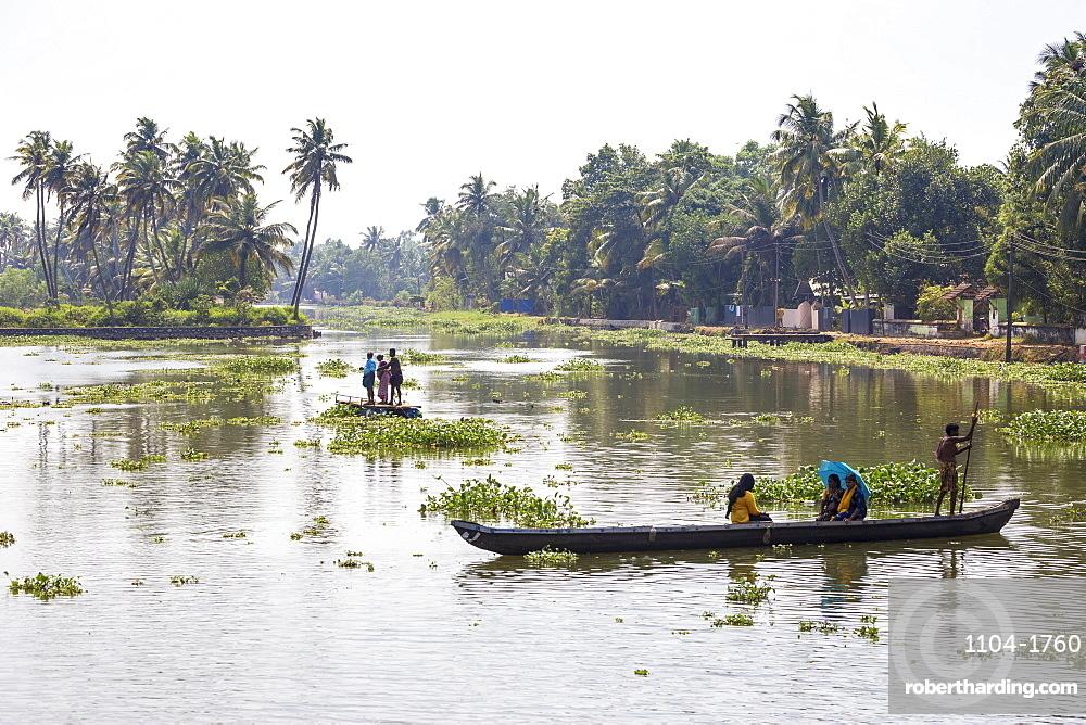 India, Kerala, Kollam, Backwaters, People crossing river in dug out canoe