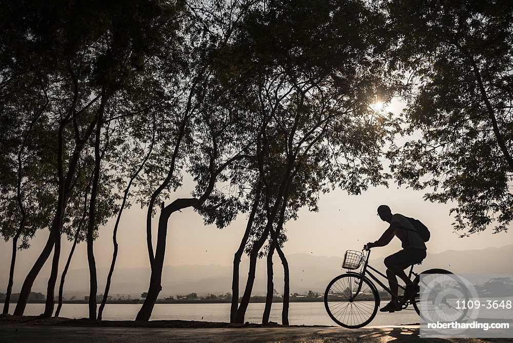 Tourist exploring Inle Lake by bicycle at sunset, Shan State, Myanmar (Burma), Asia