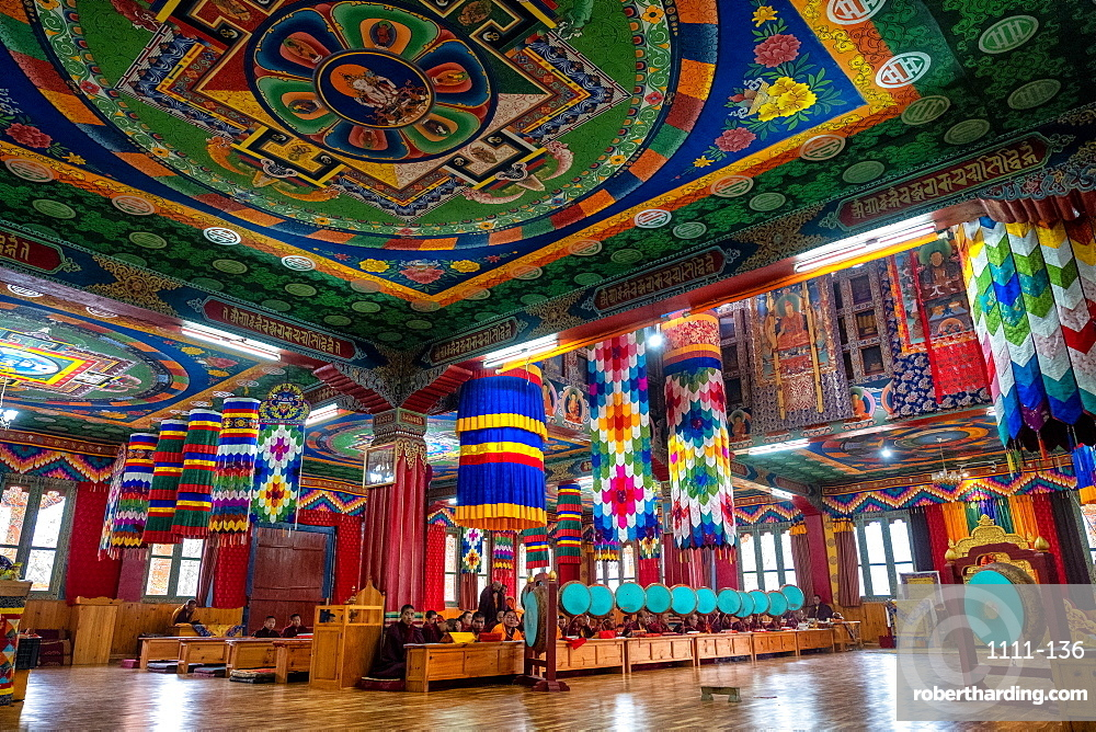 Buddhist monks worship with round gongs inside a prayer room at a monastery, Bhutan, Asia