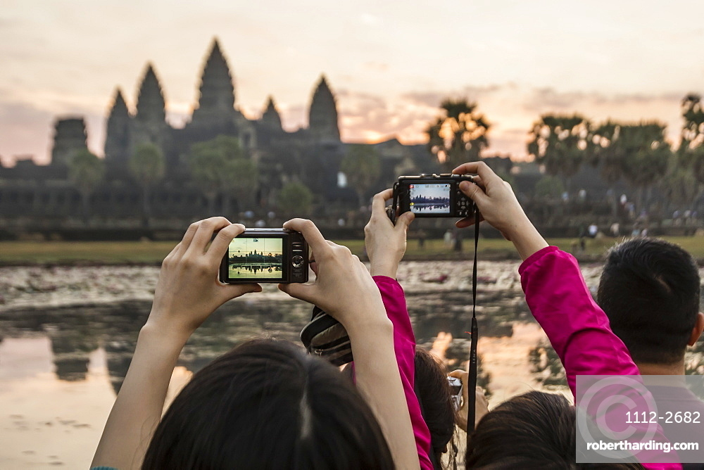 Tourists photographing the sunrise over the west entrance to Angkor Wat, Angkor, UNESCO World Heritage Site, Siem Reap, Cambodia, Indochina, Southeast Asia, Asia