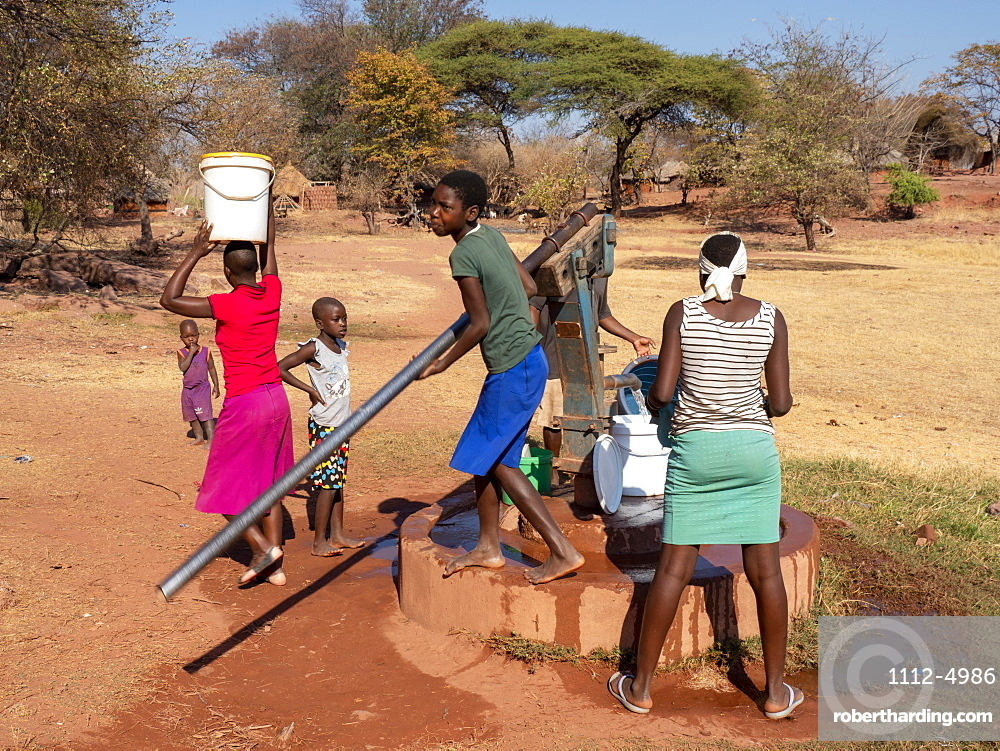 Pumping fresh water from a well in the fishing village of Musamba, on the shoreline of Lake Kariba, Zimbabwe, Africa