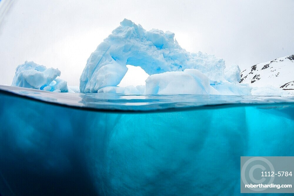 Above and below view of an arch formed in an iceberg at Cuverville Island, Ererra Channel, Antarctica.