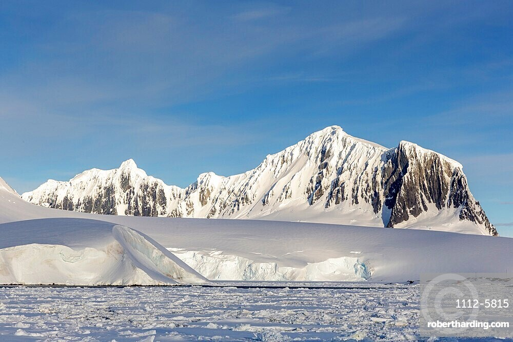 Snow-covered mountains and dense sea ice in Neumayer Channel, Palmer Archipelago, Antarctica.